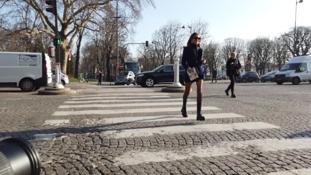 stockvideo's en b-roll-footage met helena bordon wears sunglasses earrings a blue long jacket/dress a turtleneck top a hermes bag fishnet tights black long leather boots outside elie... - coltrui