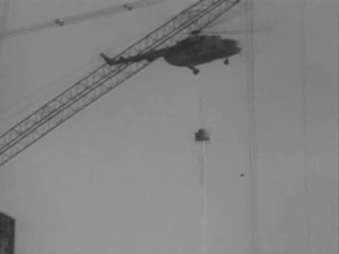 vídeos de stock, filmes e b-roll de / helicopter accidentally hitting a crane and crashing to the ground during the cleanup of the chernobyl disaster - 1986
