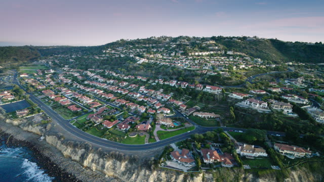 helicopter aerial flying along the pacific ocean coastal cliffs, seeing the houses in palos verdes estates, los angeles, ca, in late afternoon - palos verdes stock videos & royalty-free footage