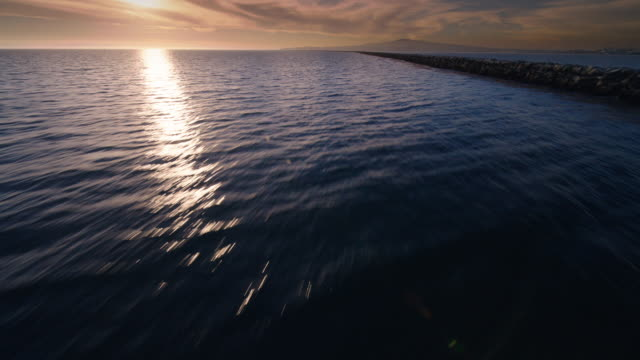 helicopter aerial flying very low over the water along the breakwater in san pedro harbor, los angeles, with a wide angle lens, seeing birds fly, looking towards the setting sun, in late afternoon - 突堤点の映像素材/bロール