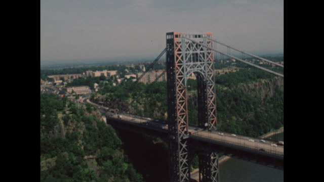 helicopter aerial shot of the george washington bridge from the 1960s era - aerial or drone pov or scenics or nature or cityscape stock-videos und b-roll-filmmaterial