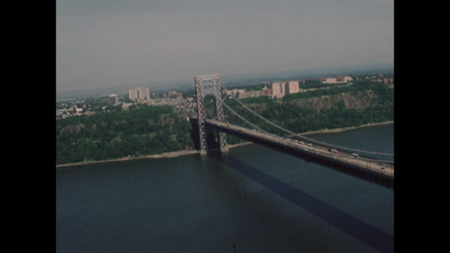 vídeos de stock e filmes b-roll de helicopter aerial shot of the george washington bridge from the 1960s era - aerial or drone pov or scenics or nature or cityscape