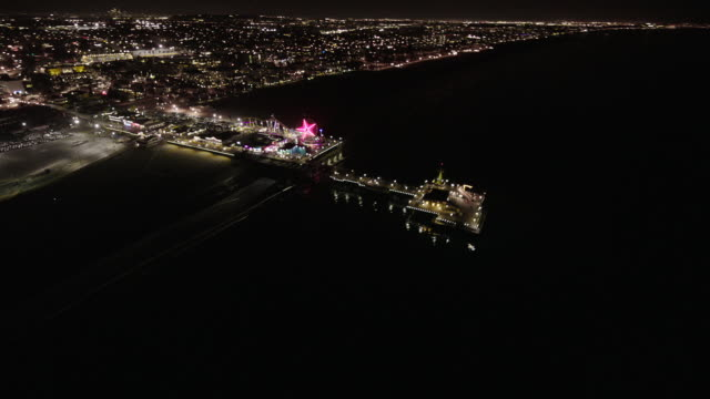 helicopter aerial, wide angle view, flying at night over santa monica, circling the santa monica pier on the pacific ocean. - santa monica pier stock videos & royalty-free footage