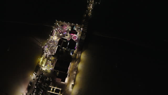 Helicopter aerial, wide angle view, flying at night over Santa Monica, looking down at, then circling the Santa Monica Pier on the Pacific Ocean.