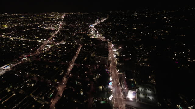 Helicopter aerial, wide angle view, flying at night over the Sunset Strip on Sunset Boulevard in West Hollywood.
