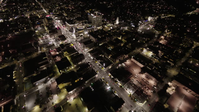 helicopter aerial, wide angle view, flying over hollywood boulevard and highland avenue in hollywood at night, seeing the hollywood-highland center, mann chinese theater, and the roosevelt hotel. - hollywood and highland center stock videos & royalty-free footage