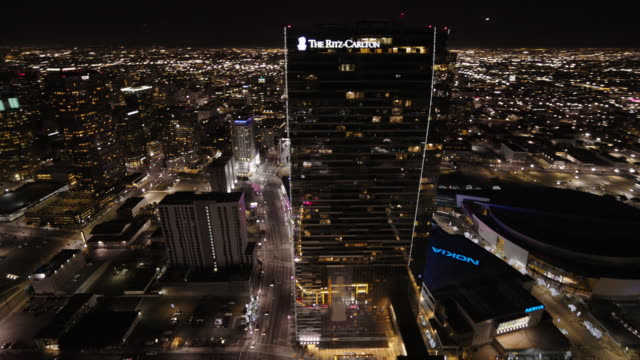vídeos de stock, filmes e b-roll de helicopter aerial, wide angle view, flying over los angeles at night circling around the ritz-carlton hotel and the jw marriott. - ritz carlton hotel
