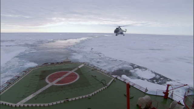 ws, helicopter approaching to helipad of icebreaker traveling through broken pack ice, russia - russia stock videos & royalty-free footage