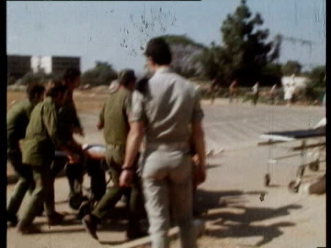vídeos de stock, filmes e b-roll de helicopter arrives to transfer wounded soldiers to stretcher / wounded taken by stretchers first days of the yom kippur war on october 07, 1973 in... - 1973