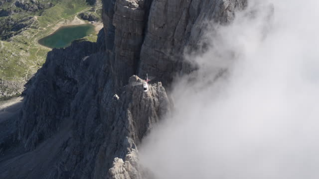 stockvideo's en b-roll-footage met helicopter ascending cliff face through fog - in de lucht zwevend