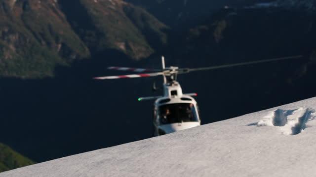 ヘリコプターは、雪に覆われた山の頂上に上る - helicopter rotors点の映像素材/bロール