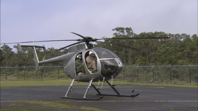 a helicopter begins to spin its rotors. - helicopter rotors stock videos and b-roll footage