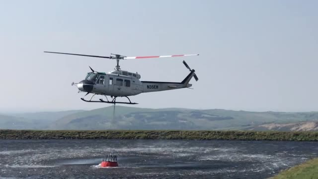 helicopter collects water to pour onto marsden moor fire in huddersfield. the fire is believed to have been started by a barbeque at easter gate, the... - national trust video stock e b–roll