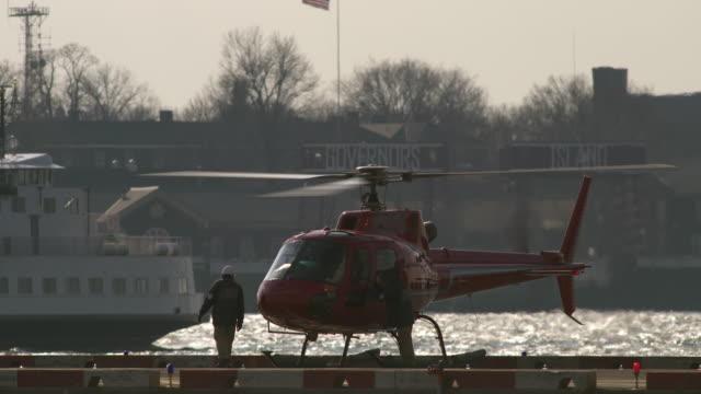 vídeos de stock, filmes e b-roll de a helicopter crew goes to unload the aircraft in slow motion. - pista de aterrizagem