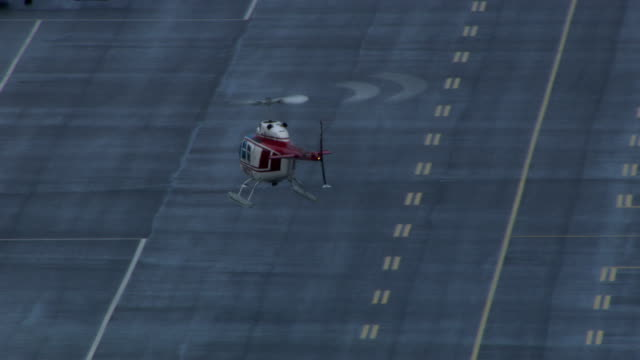 a helicopter crosses a runway and lands near another helicopter. - helipad stock videos & royalty-free footage