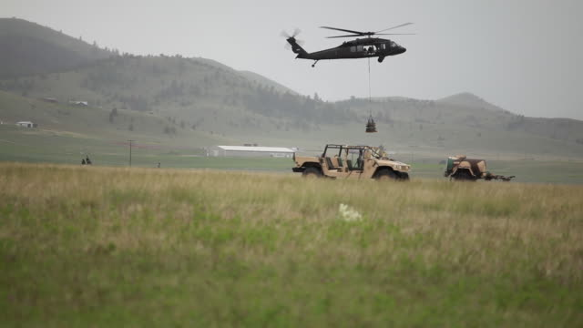 helicopter dropping cargo in field  - military helicopter stock videos & royalty-free footage