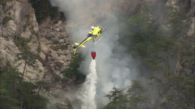 AERIAL Helicopter dropping water on forest fire in Alps, Veneto, Italy