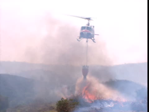 vídeos de stock e filmes b-roll de a helicopter drops a bucket of water on a brush fire. - helicóptero