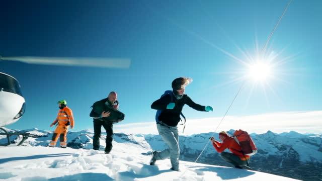 vídeos de stock e filmes b-roll de helicopter drops off mountaineers on snowy mountain summit - risco