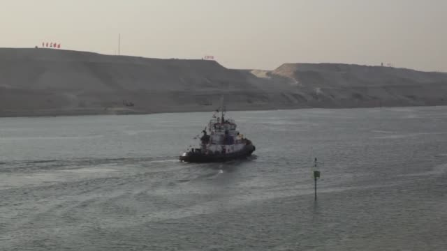 helicopter flies above vessels entering a channel which joins the old canal to the new suez canal, right, operated by the suez canal authority, in... - suez canal stock videos & royalty-free footage