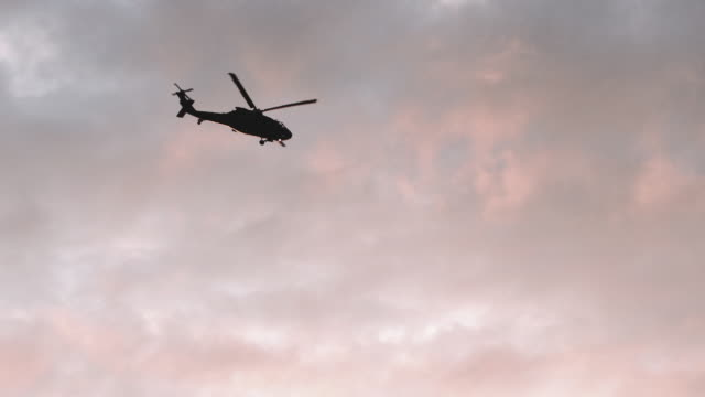 A helicopter flies along a summer sky at sunset