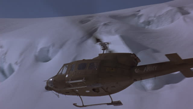 a helicopter flies alongside a mountain.  . - helicopter stock videos and b-roll footage