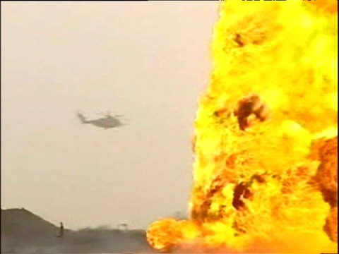 helicopter flies behind raging oil well fire in desert kuwait 31 mar 03 - kuwait stock videos and b-roll footage