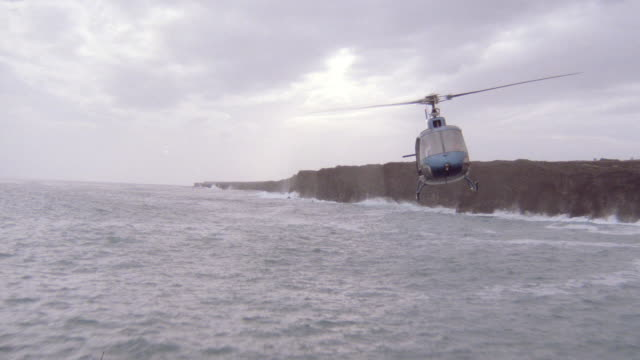 a helicopter flies low near a coastline. - pacific islands stock videos & royalty-free footage