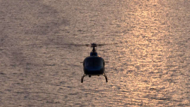 a helicopter flies low over a scenic lake. - silhouette stock videos & royalty-free footage