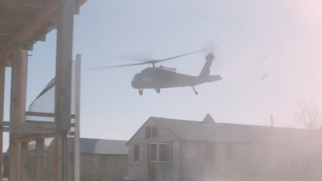 a helicopter flies low over derelict buildings in a desert town. - military helicopter stock videos & royalty-free footage