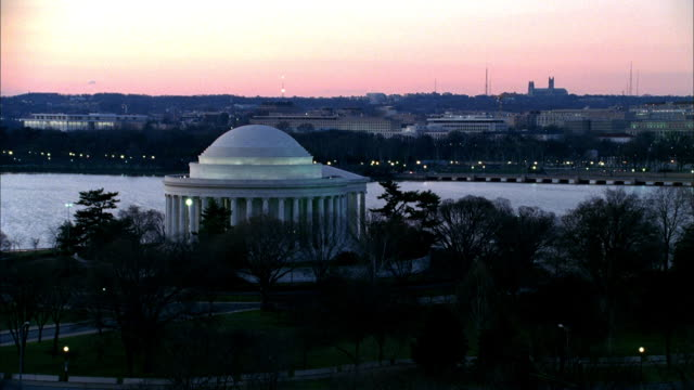 a helicopter flies near the jefferson memorial and the washington monument at sunset. - jefferson memorial stock videos & royalty-free footage