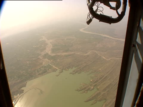 A helicopter flies over a lake and river Pakistan