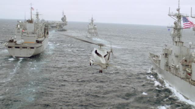 a helicopter flies over a naval flotilla. - flotilla stock videos & royalty-free footage