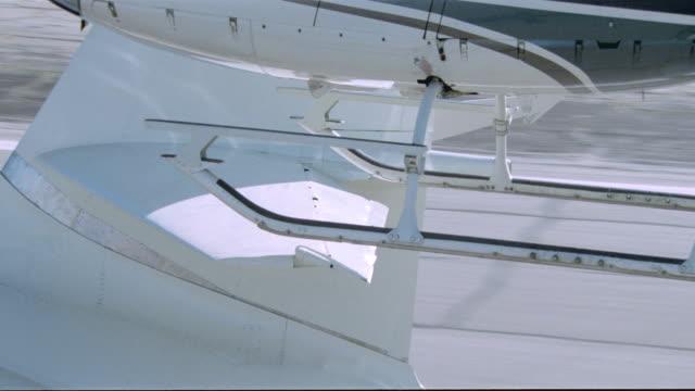 vidéos et rushes de a helicopter flies over a private jet breaking the elevator flap. - piste d'envol