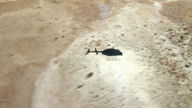 A helicopter flies over dry creekbeds in a desert landscape.