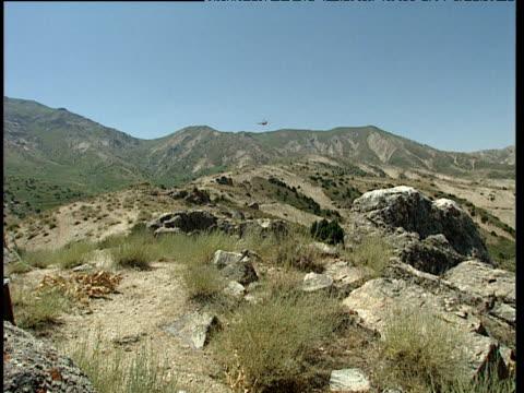 helicopter flies over mountainous region uzbekistan - ムラがある点の映像素材/bロール