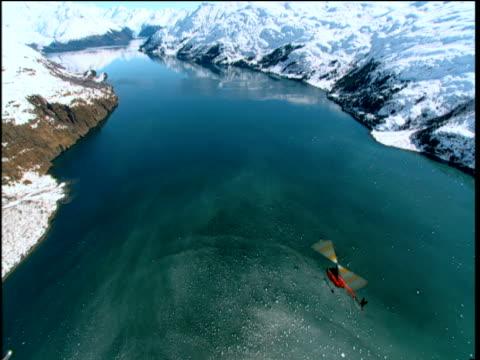 helicopter flies over river between snow capped mountains girdwood alaska - 空気力学点の映像素材/bロール