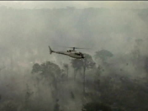 Helicopter flies over smoldering rainforest following deforestation Amazon 02 Aug 02