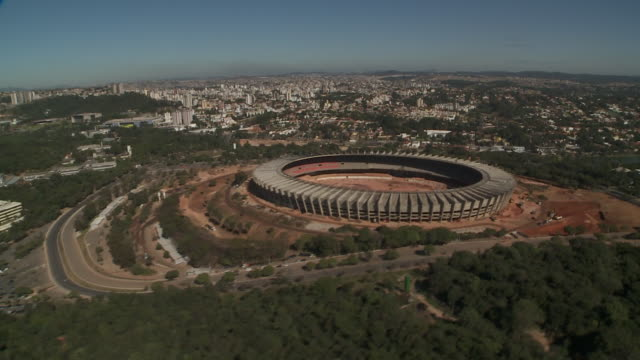 a helicopter flies over the construction site of a sports stadium in belo horizonte, brazil. - belo horizonte stock videos and b-roll footage