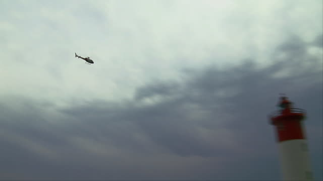 A helicopter flies over the Umhlanga Rocks Lighthouse. Available in HD.