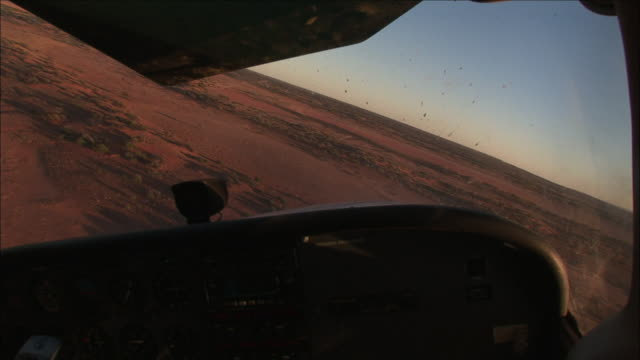 stockvideo's en b-roll-footage met a helicopter flies over the vast and dry open land of anna creek station in the australian outback. - anna creek station