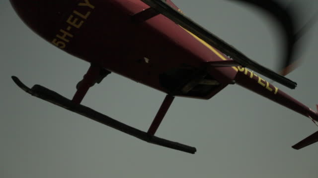 A helicopter flies overhead.