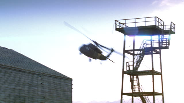 a helicopter flies past a military prison camp in the desert. - barracks stock videos & royalty-free footage