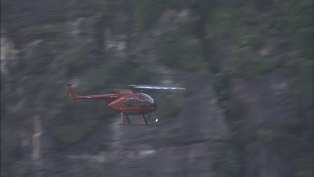 A helicopter flies past cliffs near Angel Falls.