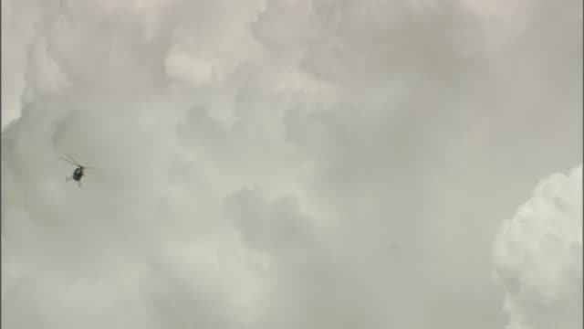 a helicopter flies past clouds of volcanic ash. - ash stock videos & royalty-free footage