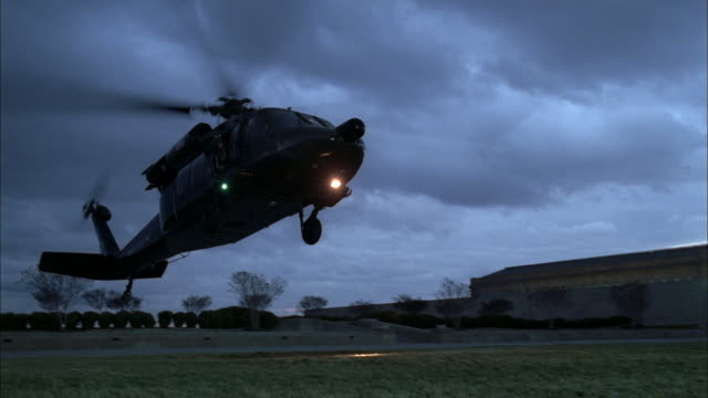 a helicopter flies through a gray sky and lands in a grassy field at the pentagon. - united states department of defense stock videos & royalty-free footage