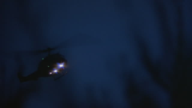 a helicopter flies through a night sky. - helicopter stock videos and b-roll footage