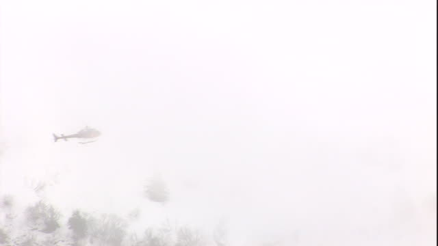 a helicopter flies through a snow storm in a mountainous area. - land stock videos & royalty-free footage