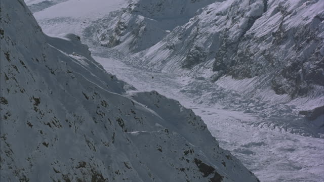 Helicopter flies through snow covered valley.