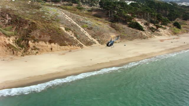 日差しの中でロング ビーチの上を飛んで空中のヘリコプター - 活動点の映像素材/bロール